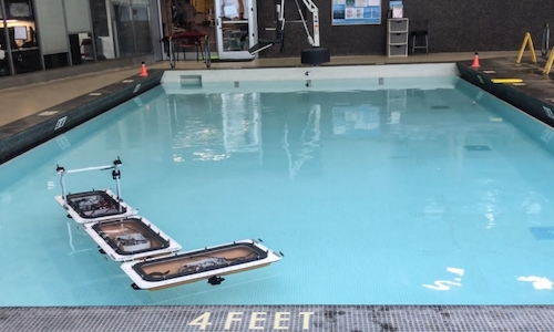 A photo of MIT's robotic boats floating in a pool.